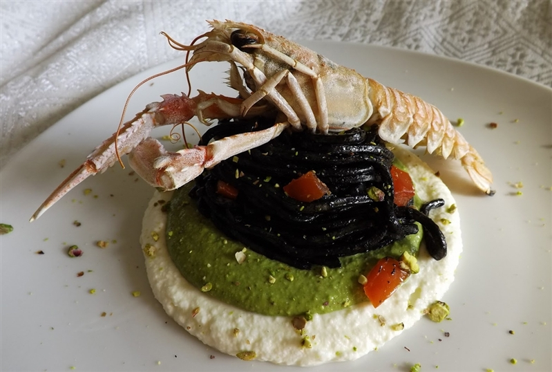 Cuttlefish ink spaghetti alla chitarra with bronte pistachios mousse and buffalo mozzarella with scampi