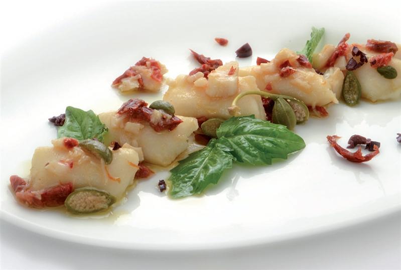 Gnocchi ripieni di provola con pomodoro secco, baccalà, olive e capperi in fiore