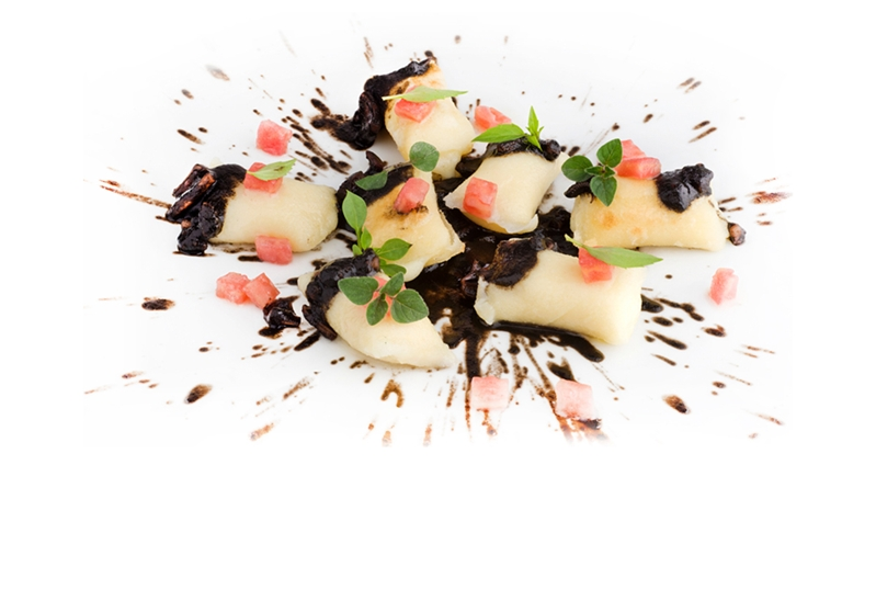 Gnocchi stuffed with provola in two cookings, with black squid ragù and tomato concasse