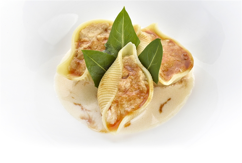 Conchiglioni stuffed with rabbit in genovese sauce served on smoked provola cheese sauce