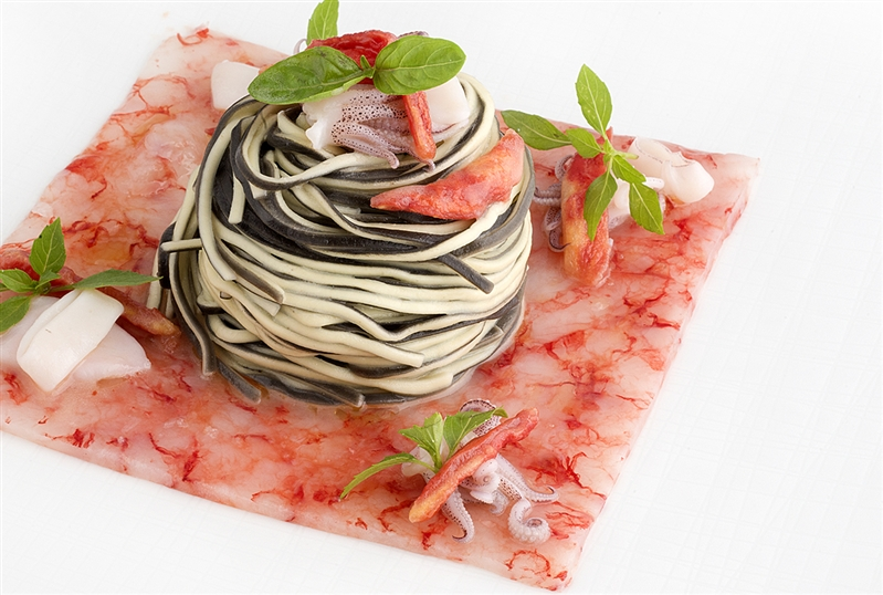 Amorini su carpaccio di gamberi di Crapolla con calamaretti spillo e pomodori canditi